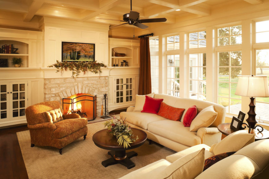 This living room has high built-in shelving bookending a fireplace. Built-in shelving is not only useful for sorting items but it can make good use of a space that would otherwise be left blank. Filling these spaces with shelves can make the room feel fuller and more cozy.