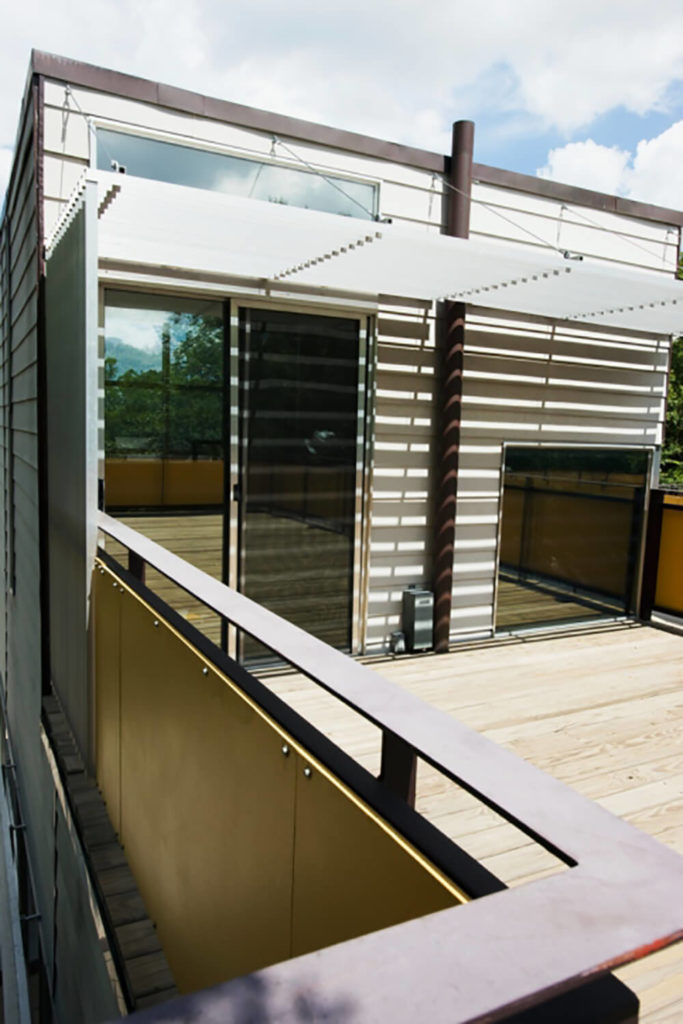 A flat railing is combined with metal panels, creating a private and strong barrier between the second story deck and the drop-off.