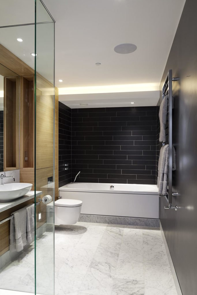 The bathroom is awash in high contrast, tactile elements, with black tile walls, rich natural wood cabinetry, marble flooring, and a floating vanity with vessel sink.