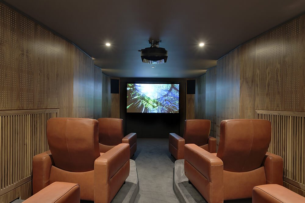 A very charming home theater with stylish wooden walls and gray carpet flooring.