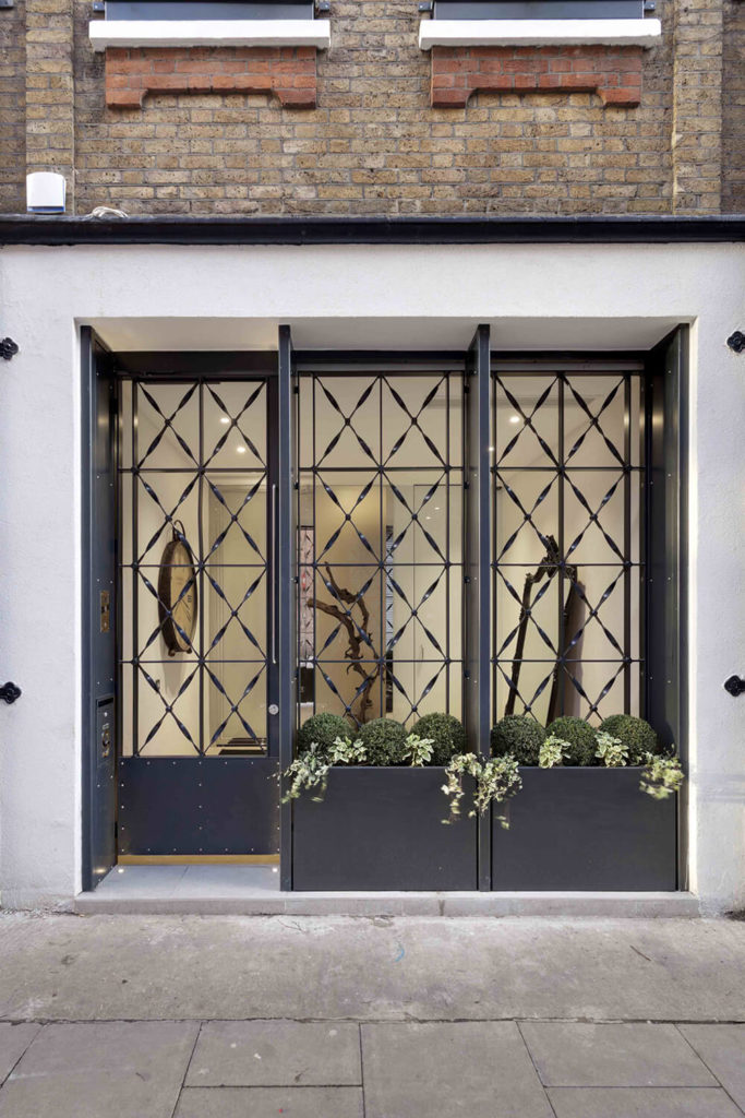 Here's a peek into the entryway, appearing at street level like the entrance to a classy shop or business. The decorative metal screen offers privacy and even space for a small garden.