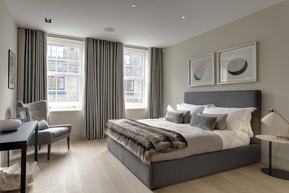 Medium-sized primary bedroom featuring hardwood flooring and gray walls matching the gray window curtains and gray bed frame.