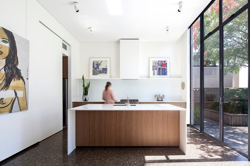 The kitchen centers on a large island wrapped in white, with natural wood accents and cabinetry seen throughout in counterpoint to the expanses of bright white. Even here, artwork adorns many surfaces, granting the home its sense of style.