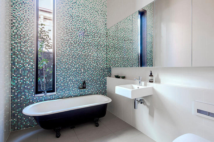 The primary bath also features an intricate tile wall, this time providing a wash of color in the white space. Frameless mirrors and a claw foot bathtub make for intriguing juxtapositions in this modern space.