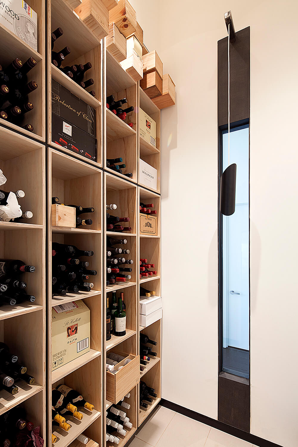 The home boasts a suite of features like this large wine storage room, stacked to the ceiling with cubic natural wood shelving.