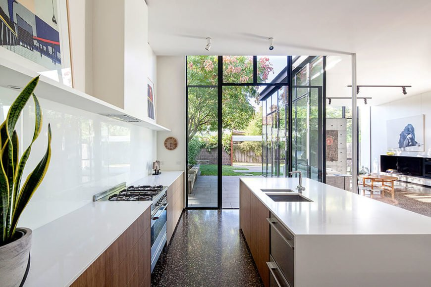 Moving inside, we see how the full height glass makes for an effortless transition between indoors and out. The surfaces throughout the addition are sleek and minimalist, with white walls over smooth concrete flooring throughout.