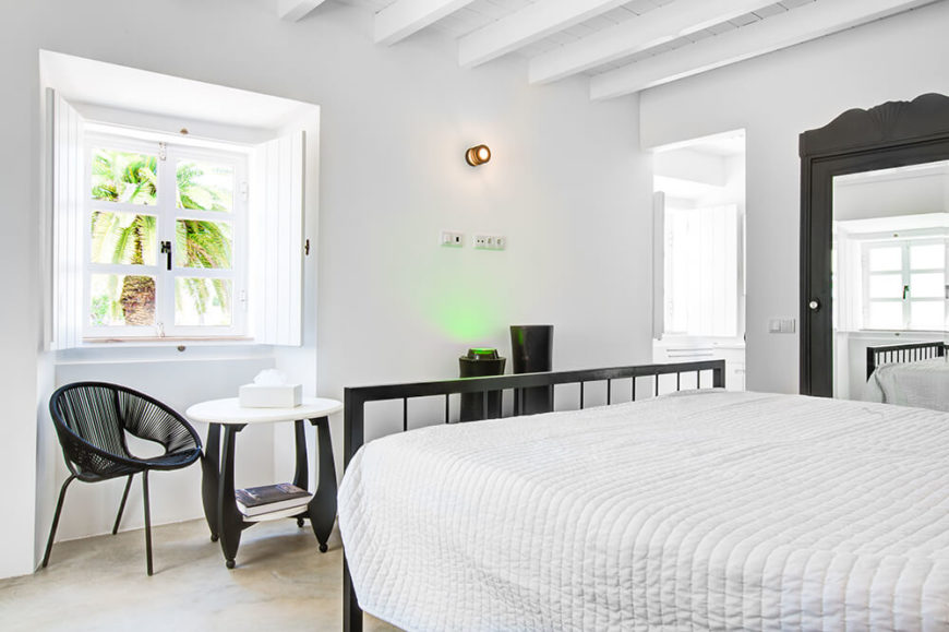 The primary bedroom is unified by sharp black accents on the furniture, including bed frame, chairs, and mirror frame. Even here, the large windows spill abundant sunlight into the bright white space.