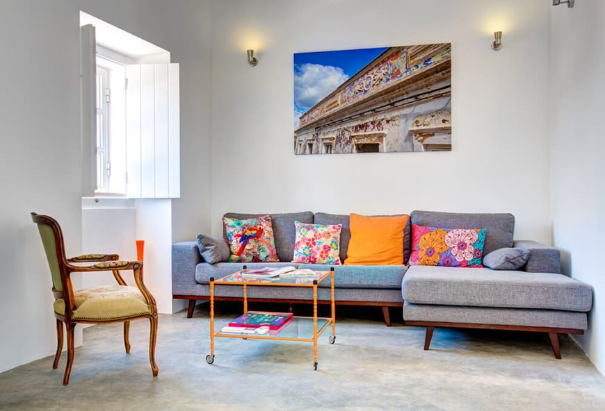 Moving inside, we see our first example of the subtly placed but riotous color injected in the home. This midcentury modern sectional is spiked with brightly colored pillows, wrapping a glass and bright orange metal coffee table at center.