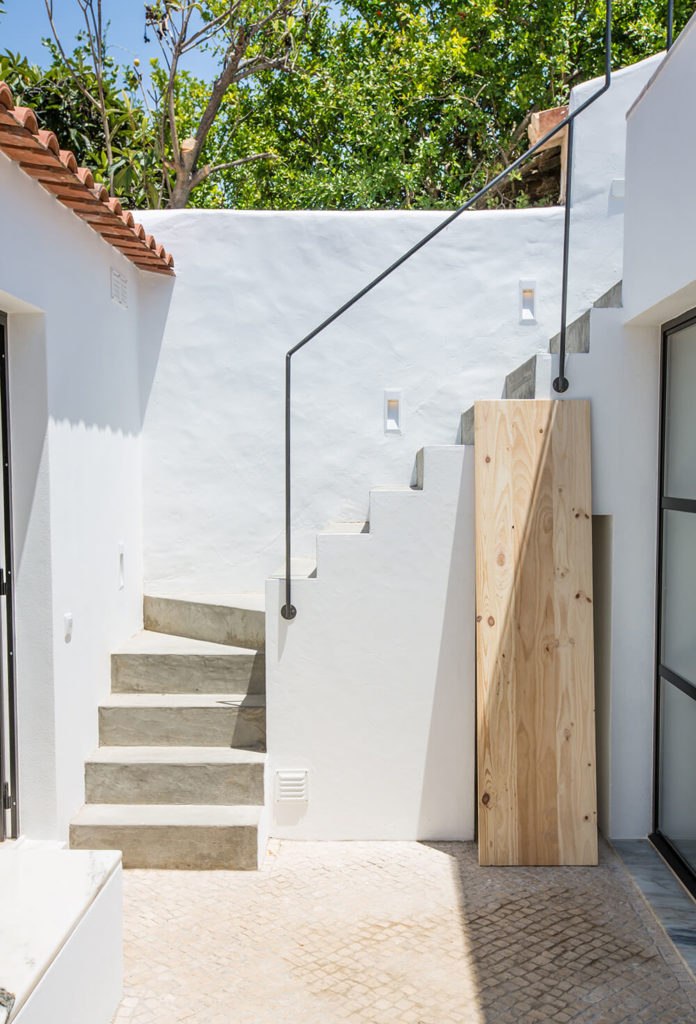 The low level exterior patio seen here is accessible both via glass sliding doors from inside the home and a staircase that leads to upper level exterior spaces with expansive views.