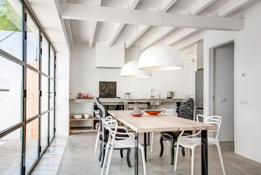 The large open plan kitchen and dining room area features more restrained use of color, mostly kept to the natural wood dining table and a few colorful accents. The rugged look of the natural wood countertops and shelving offers a counterpoint to the sleekly modern white walls.