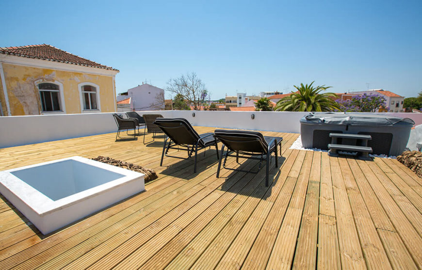 Finally, we reach the rooftop patio space, decked with natural wood and sporting a jacuzzi with full expansive views of the surrounding homes and countryside. A skylight offers a brief glimpse down into the home.