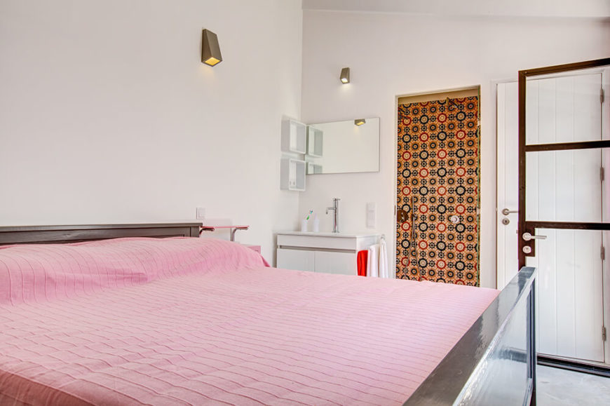 This secondary bedroom centers on a massive modern bed frame with subtle pink sheeting. An attached bathroom is accessed through a highly patterned yellow door, next to a small white vanity area.