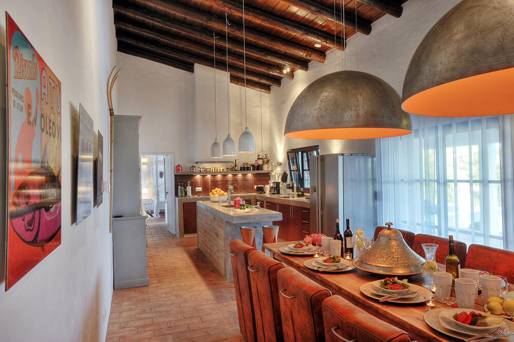 Large kitchen area featuring beautiful brick tiles flooring that matches the center island, which features a thick marble countertop similar to the kitchen counters. The lighting looks amazing together with the ceiling with beams.