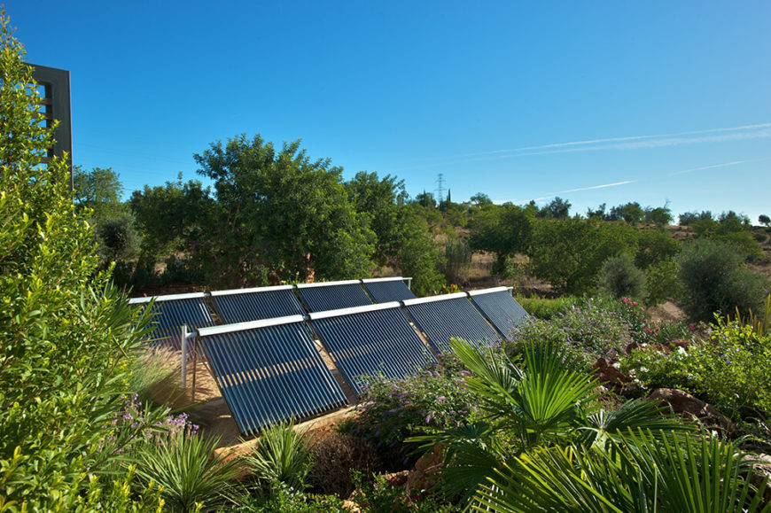 Nestled deeply in the lush vegetation surrounding the patio, we see rows of solar panels. These help to power the home, taking advantage of the sunny Portuguese climate for a more sustainable lifestyle.