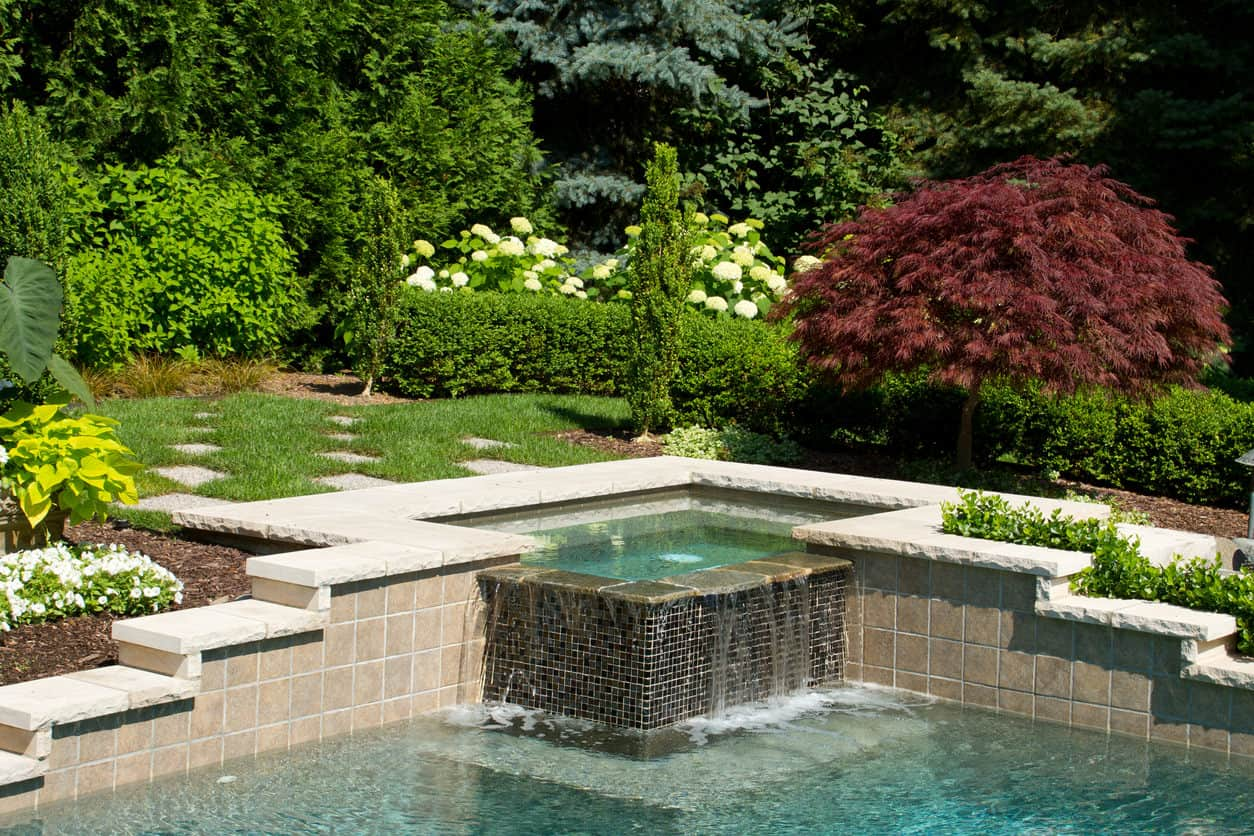A black mosaic corner hot tub integrated to the pool and lined with beige marble. It has a perfect lush outdoor scenery that will let you relax and unwind.