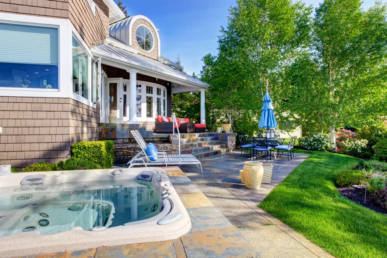Modern hot tub lined with stones that compliment the stairs leading to the house. It is set on a concrete platform bordered by green lawn that separates from the beautiful garden.