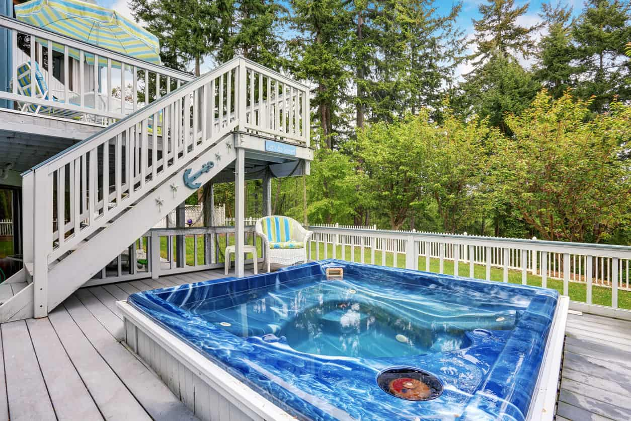 Another modern hot tub surrounded by light wood plank deck with stairs that lead to the balcony.