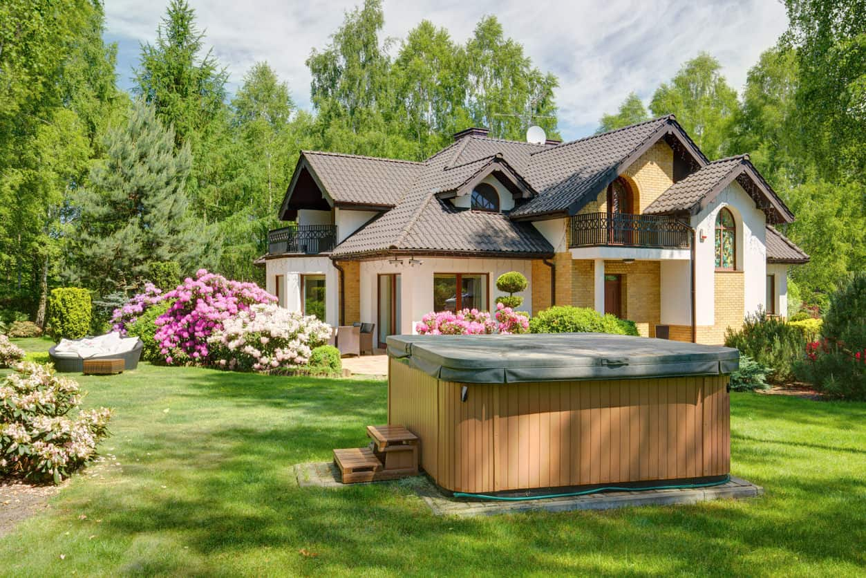 A hot tub framed with wood planks sits in on a concrete platform in the middle of the green lawn. With its lovely garden and towering trees, you'll get to relax with peace with an assurance of privacy.