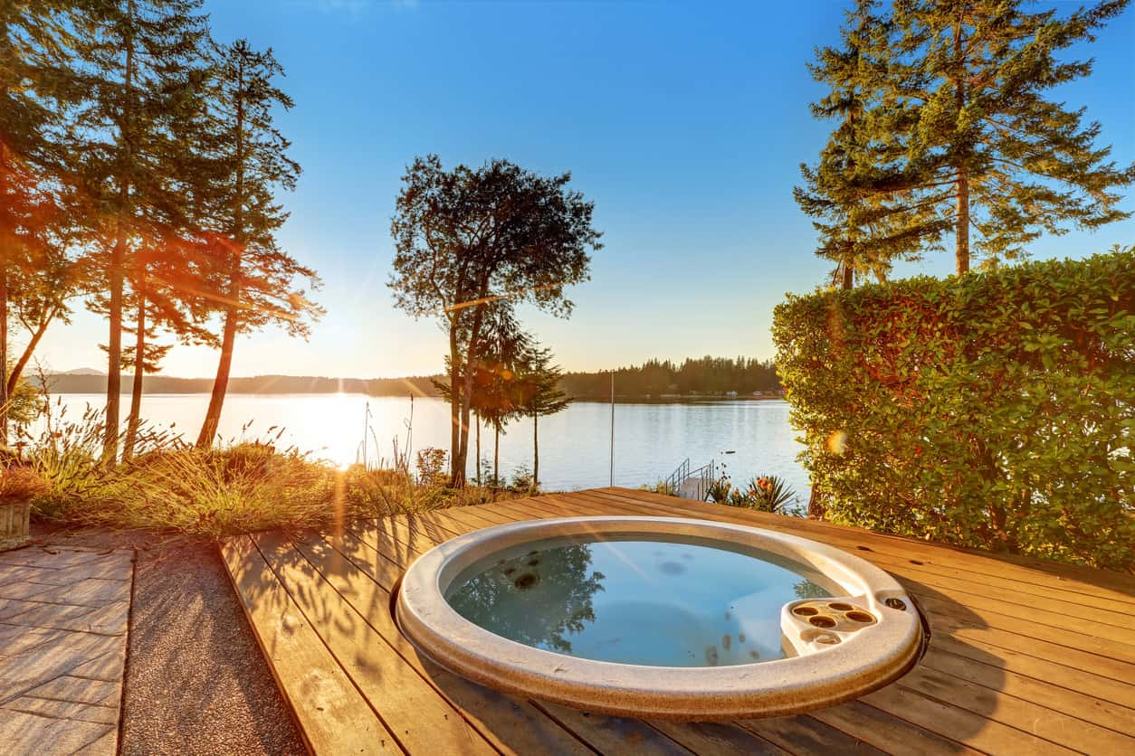 Small round tub fixed on a wooden plank deck with a spectacular view of the beach and a crystal clear view of the sunset.
