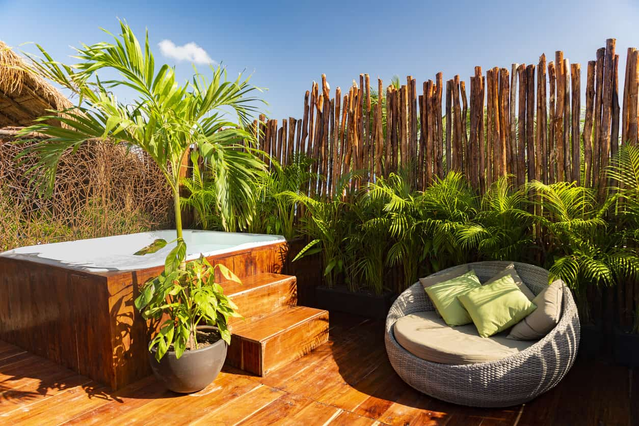 Bamboo walls with plants surrounded this square hot tub with steps beside a round rattan lounge chair making you feel you're one with nature.