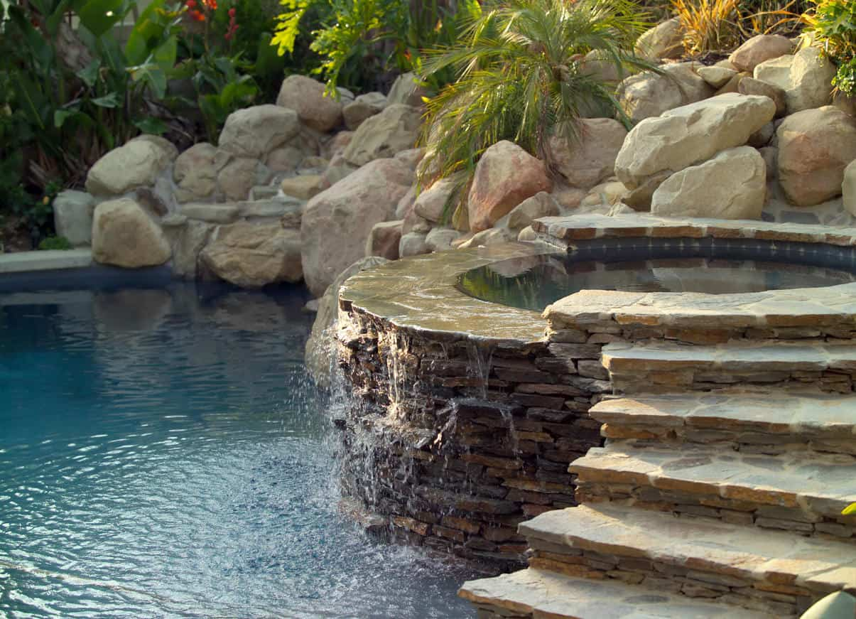 Gorgeous round stone hot tub with steps going to the pool. It is highlighted by huge stones that serve as its background and accented by greeneries.