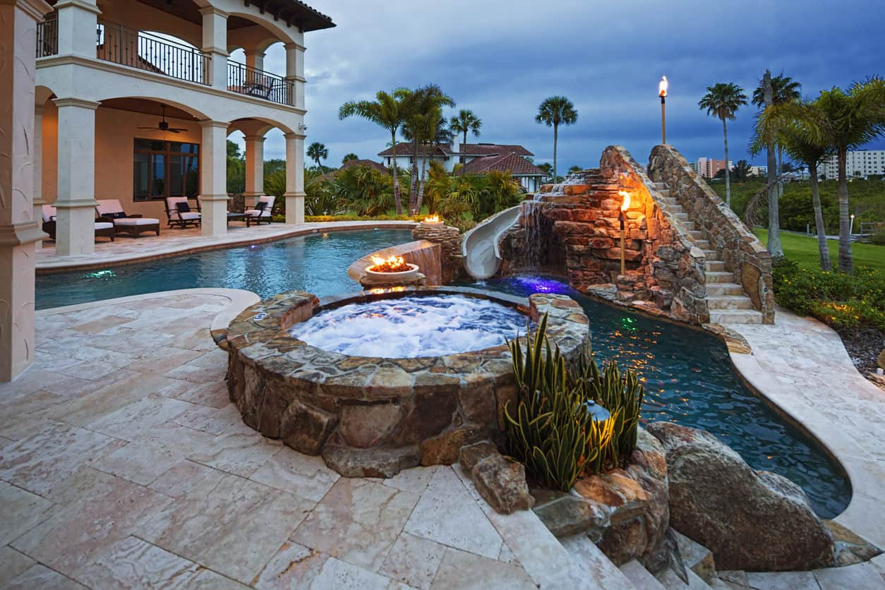 A round stone hot tub attached to a stunning pool faces the water slide with fountain. Fire pits and torches create a warm ambiance along with the serene view.