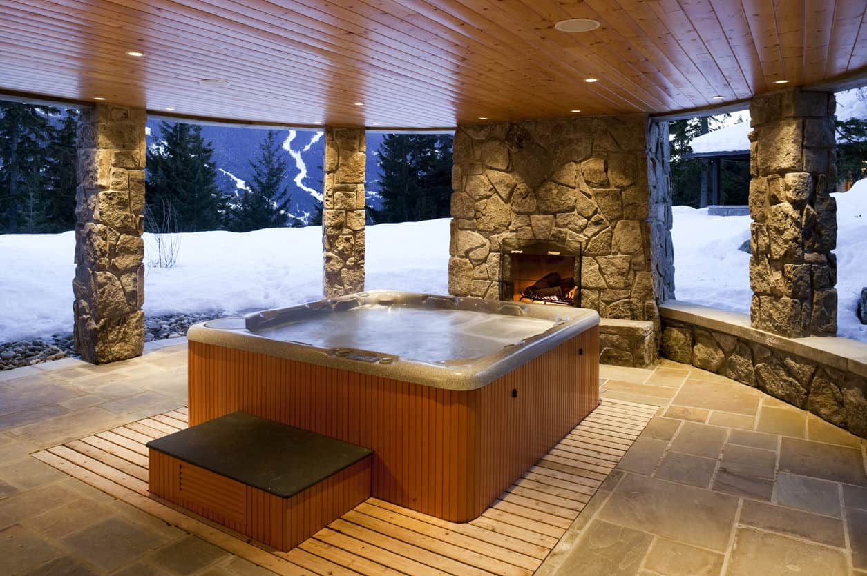 Warm yourself up in this cozy freestanding hot tub framed with wood planks and surrounded by stone pillars. It has a fireplace fixed into the stone wall to make sure you'll get that warm bath.