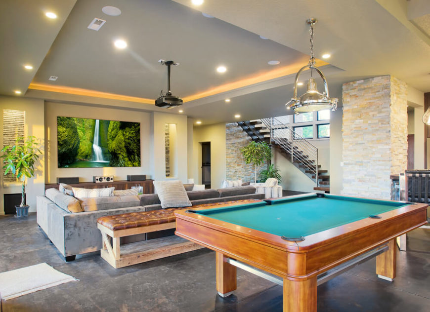 This walk-out basement features a tray ceiling with a projection system along with a billiards table to the other side. The space is neatly divided into different areas, each with a purpose.