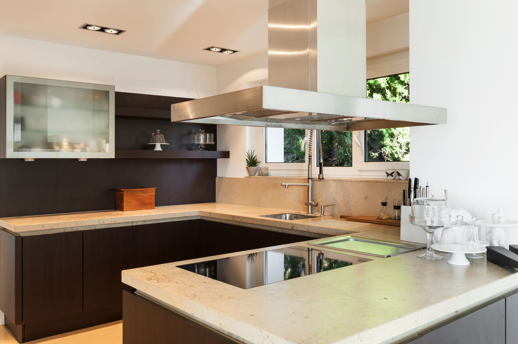 Subtle concrete countertops in a light patina. The countertops are punctuated by a ceramic cook top and an industrial style stainless steel sink.