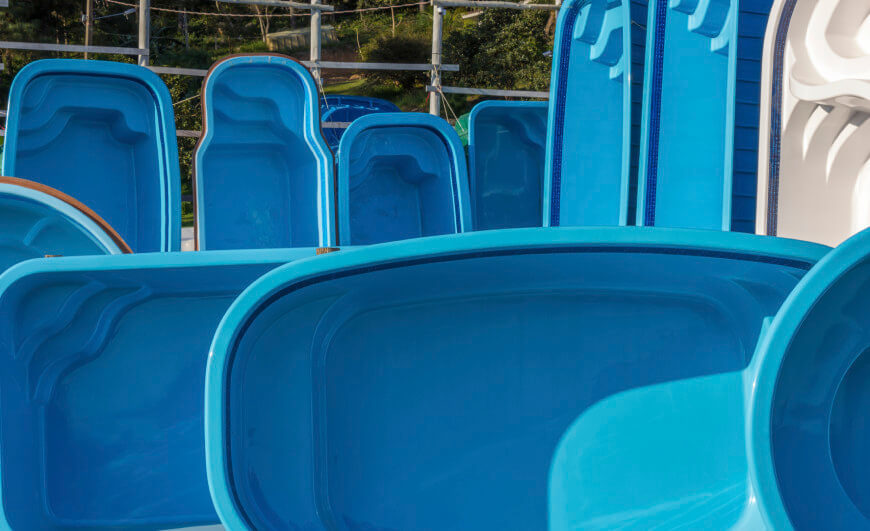 Here are some fiberglass pools laying on their sides, ready for delivery and installation.