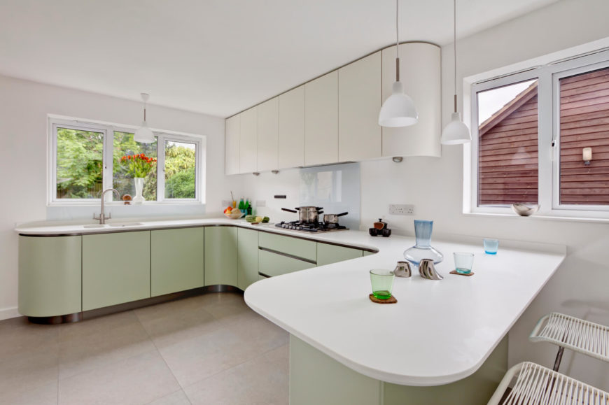 Smooth white laminate countertops in a modern kitchen. The lower cabinets are in a pale pastel green.