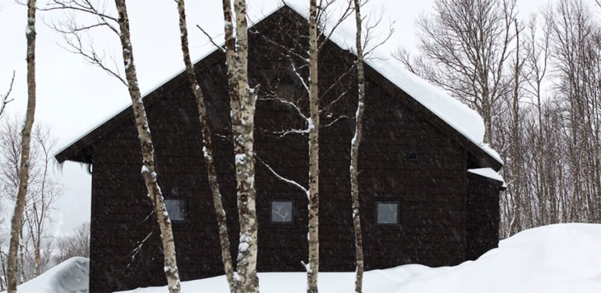 Here we see a set of smaller windows on the side of the home, punctuating the black exterior beneath and above heavy snow. The simple structure belies a sophisticated interior.