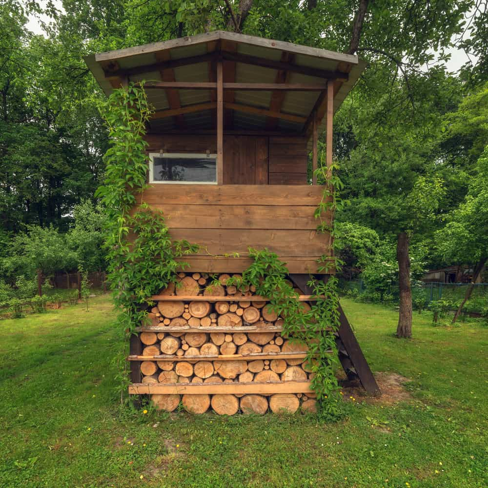 Elevated playhouse with firewood storage underneath.