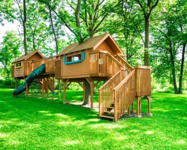 Incredible playhouse structure that is two playhouses connected by bridge and includes a slide.