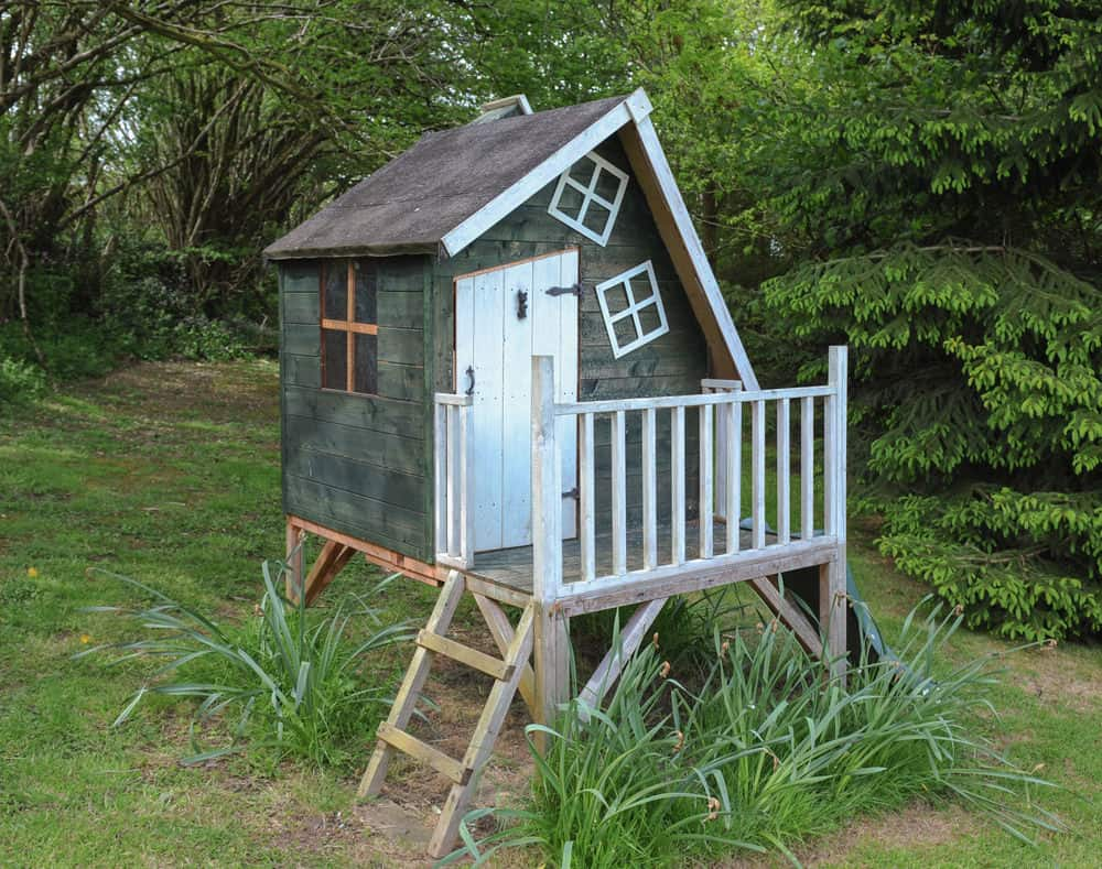 Small crooked playhouse with front porch in green and white.
