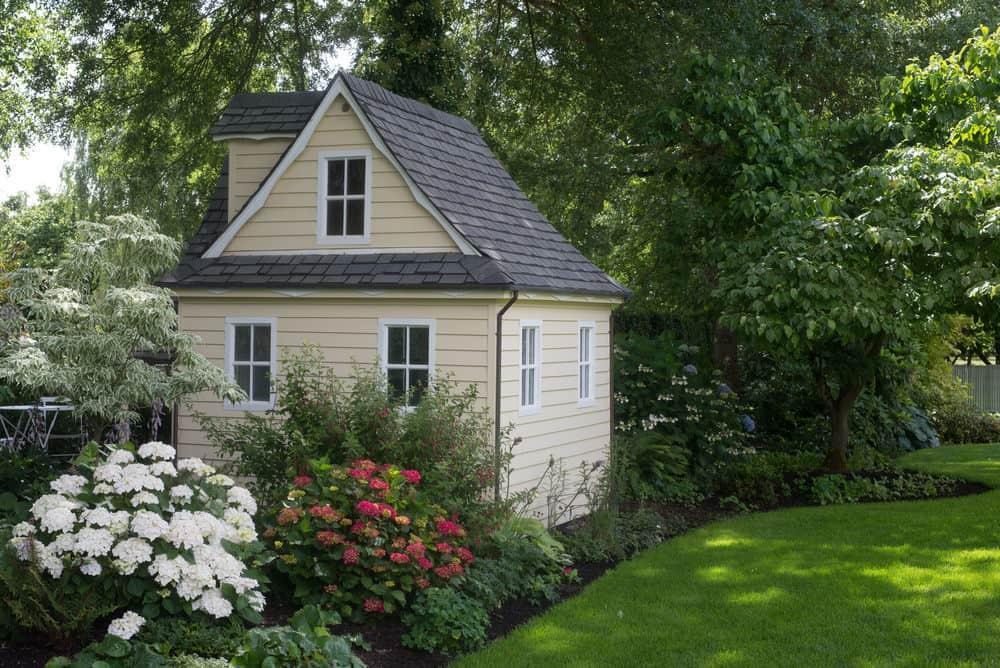 Quaint light yellow playhouse with dormer window set in garden in the backyard.