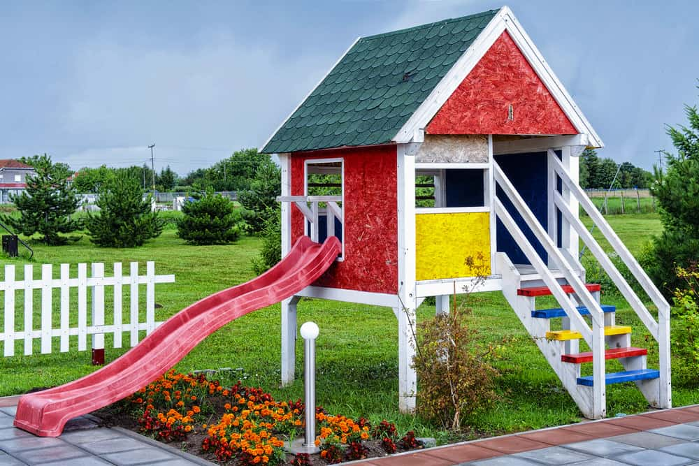 Red and yellow playhouse elevated on stilts with red slide and multi-colored staircase.
