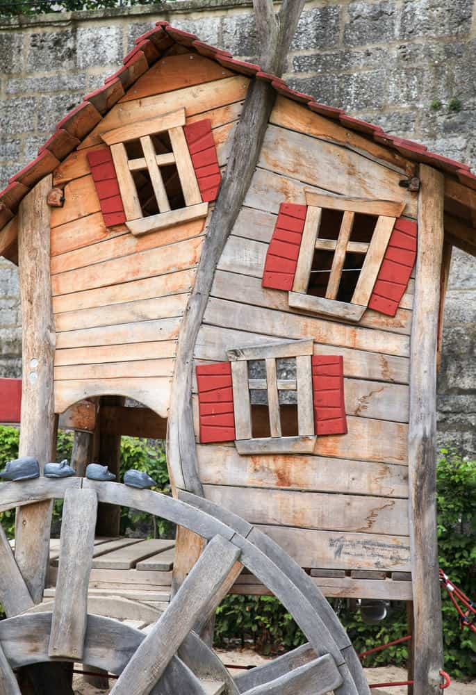 Close up of a crooked playhouse with windows and red shutters.