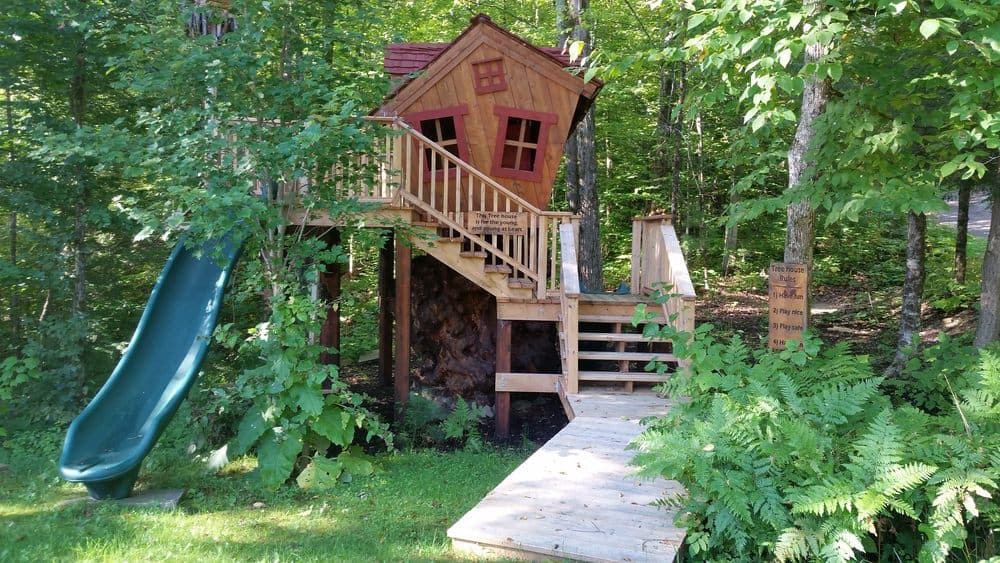 Crooked playhouse elevated on stilts with deck.