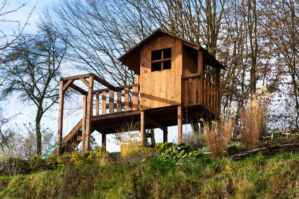 Incredible wooden playhouse on stilts with porch and deck and slide.