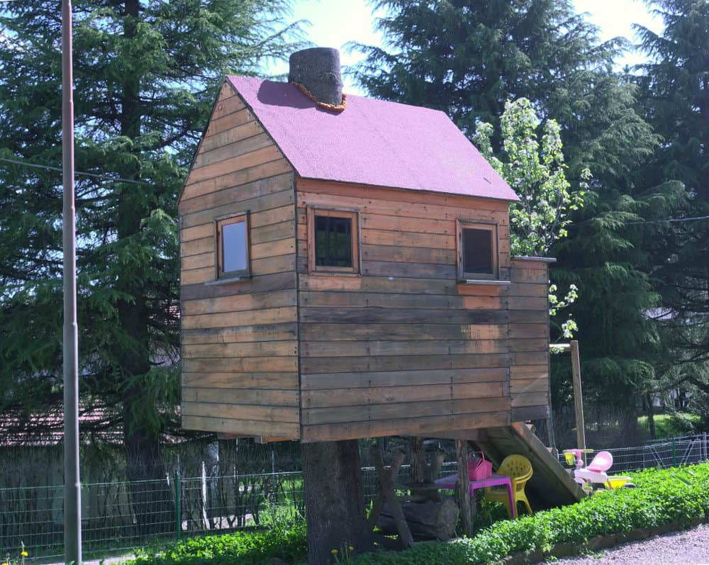 Wooden playhouse on stilts with pink gable roof.