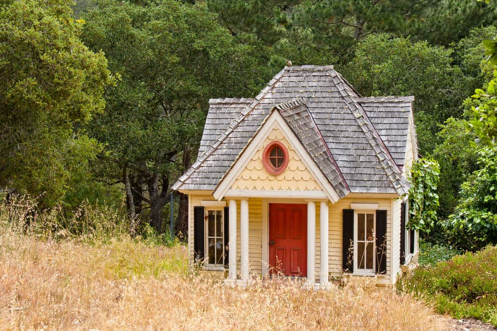Gorgeous Victorian style yellow playhouse with white columns and red door.