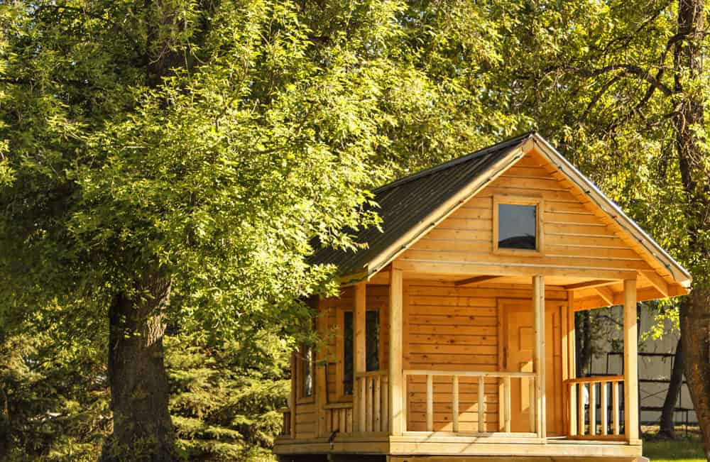 Nicely crafted natural wood playhouse with front porch.