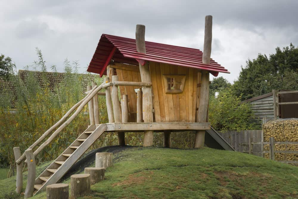 Cool playhouse with huge log beams and red roof.