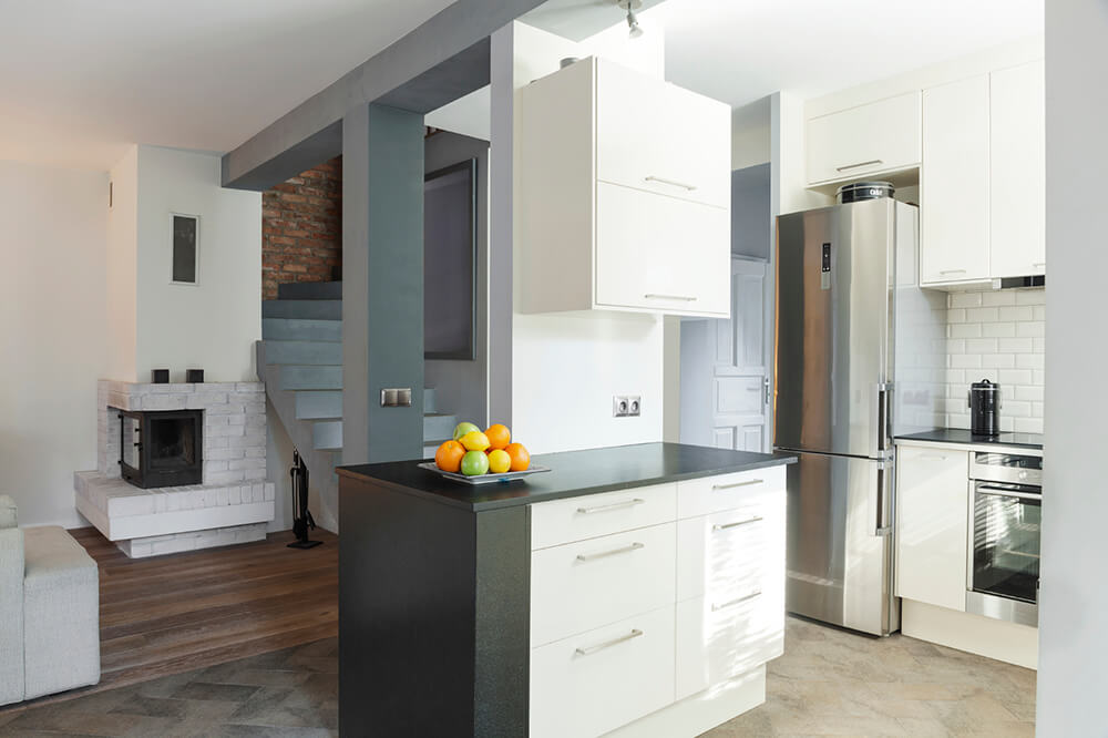 Designed open kitchen and drawing room interiorThe stone floor of this kitchen has varying textures and colors and is arranged in a herringbone pattern.