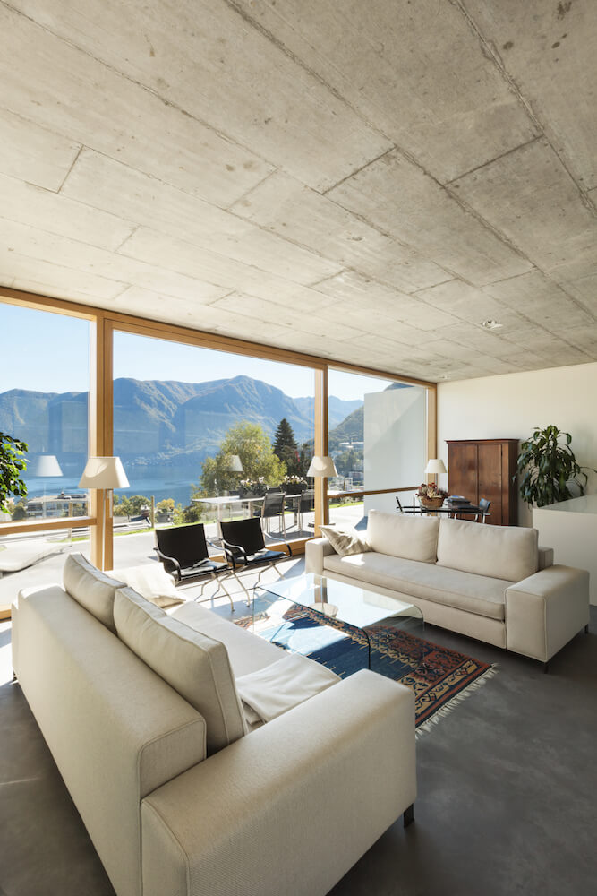 Concrete ceiling tiles have the effect of modernity, which is perfect for an open living room with floor-to-ceiling picture windows and a muted color scheme.