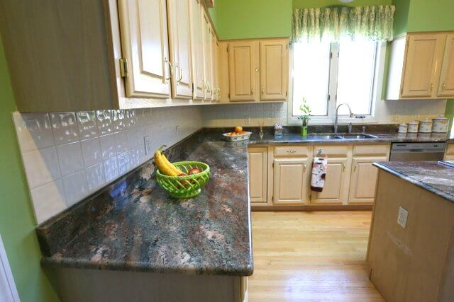 The jewel tones of this granite draw the eye. Peacock blue and brown stand out against the lightly textured white tile backsplash.