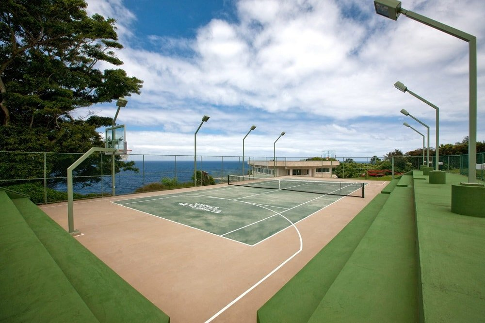 This is a view of the tennis court that also doubles as the basketball court. It has a view of the ocean on one side and green bleachers on the other side. Image courtesy of Toptenrealestatedeals.com.