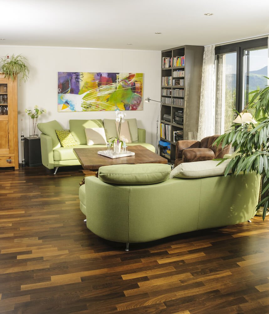 Short, narrow planks in various shades add to the natural, earthy color palette of this casual living room. Soft green furniture and plenty of houseplants contribute to the natural, earthy effect.