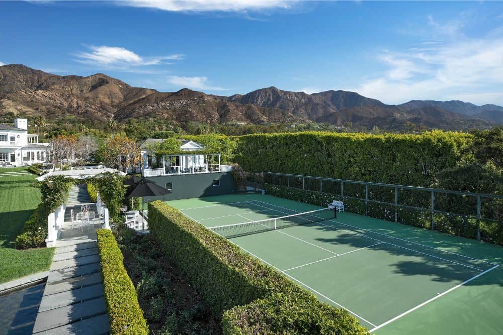 This green tennis court is complemented by its tall lush green hedges of shrubs surrounding the court. Images courtesy of Toptenrealestatedeals.com.